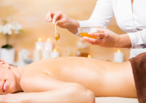 Woman enjoying spa treatment with honey