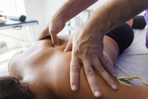 Fisioterapeuta trabajando los hombros de una joven deportista. Quiromasajista teraputico trabajando. Tratamiento de sobrecarga muscular.